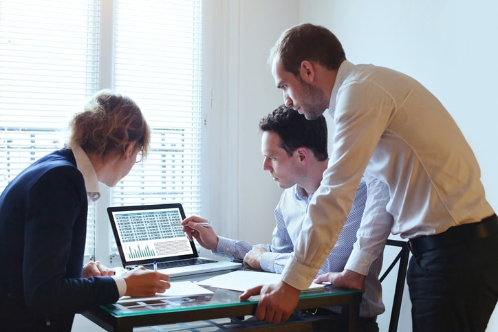 Male and female workers looking at data on a computer screen